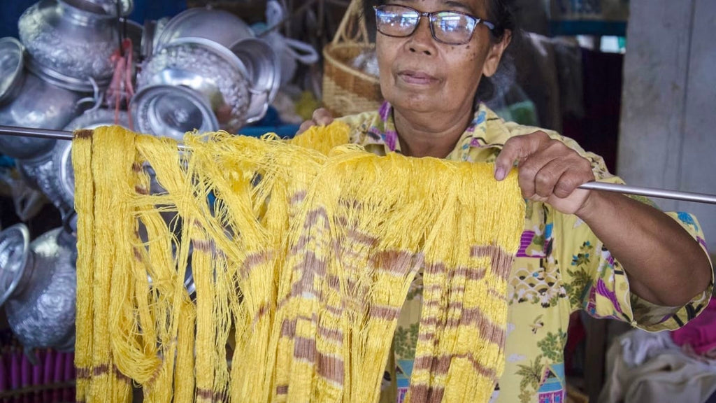 Pure silk yarn in mellow yellow colour being hung to dry after the Ikat dying process ready for weaving - Rare & Fair