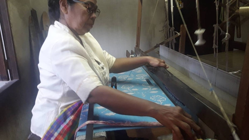 A Thai Artisan on a traditional loom crafting pure silk ikat fabric with a floral pattern for the Chermarn ikat mini dress - Rare & Fair.
