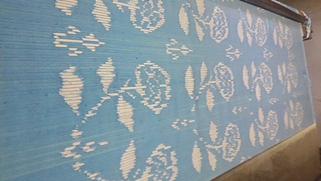 Pure silk on a traditional loom showing a floral ikat print. The 100% silk fabric is being prepared for the Chermarn Ikat Mini Dress in Sky Blue by Rare & Fair
