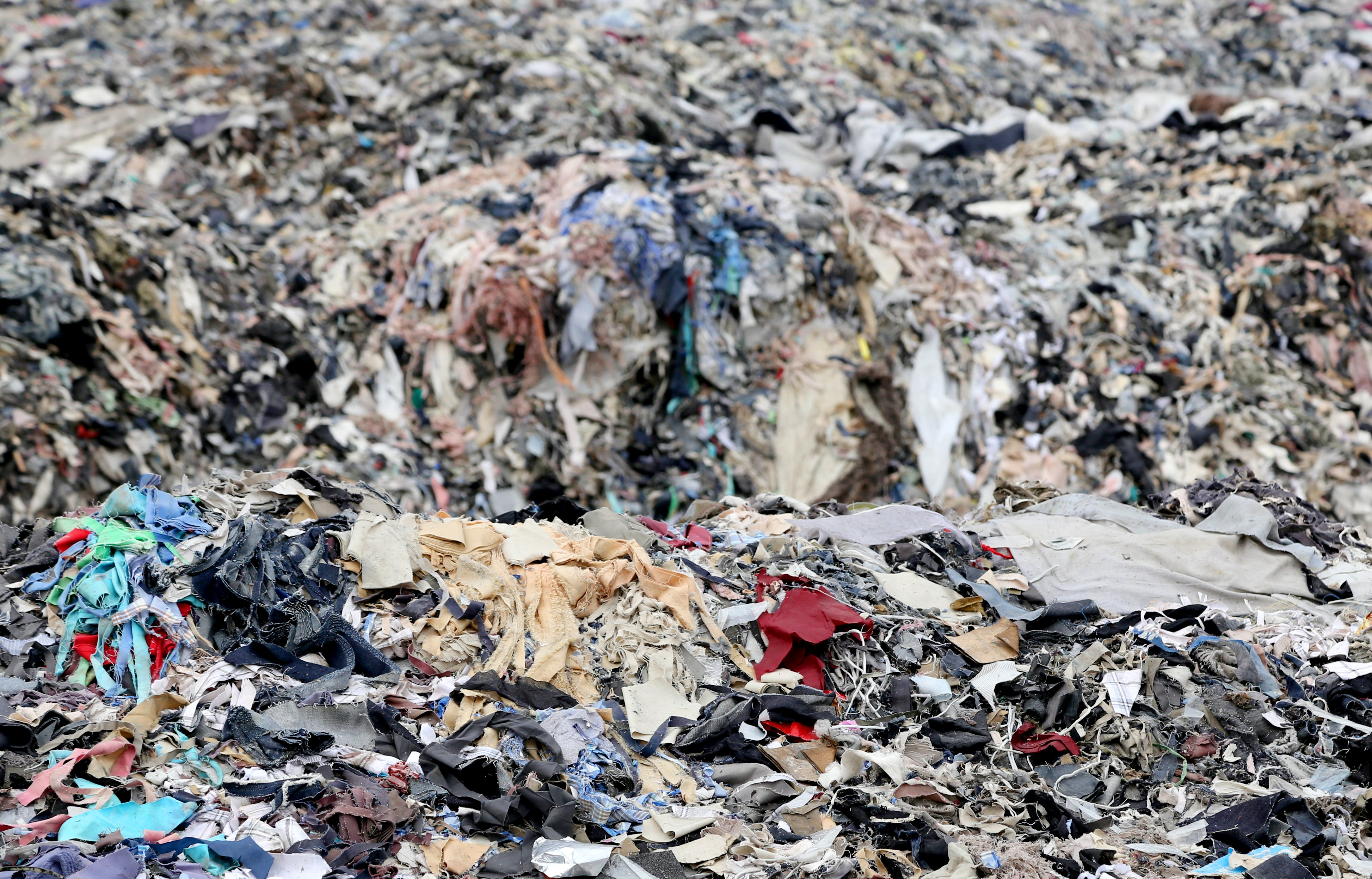 Large pile of clothing and textile waste in landfill