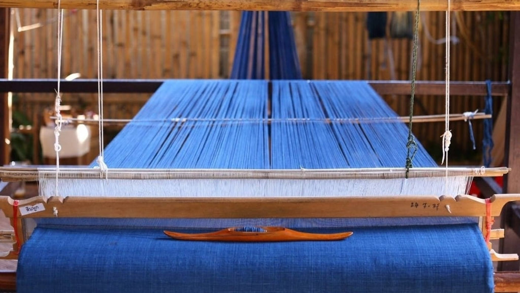 Image of blue fabric on a handloom midway through weaving.