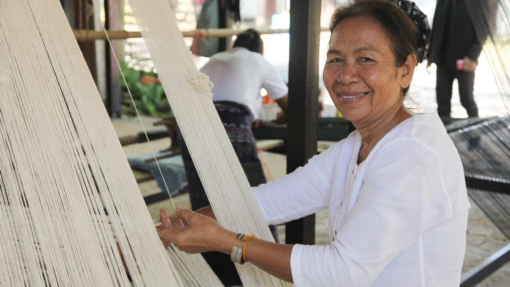 An artisan at Tohsang Cotton Village prepares the un-dyed, hand-spun naturally grown cotton for weaving on a traditional loom for the Handmade Chloe Blazer Dress by Rare & Fair