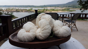 Yarn balls of sustainable, natural cotton with the Mekong River in the background. The image is taken at Tohsang Sustainable Cotton Village in Thailand for Rare & Fair.