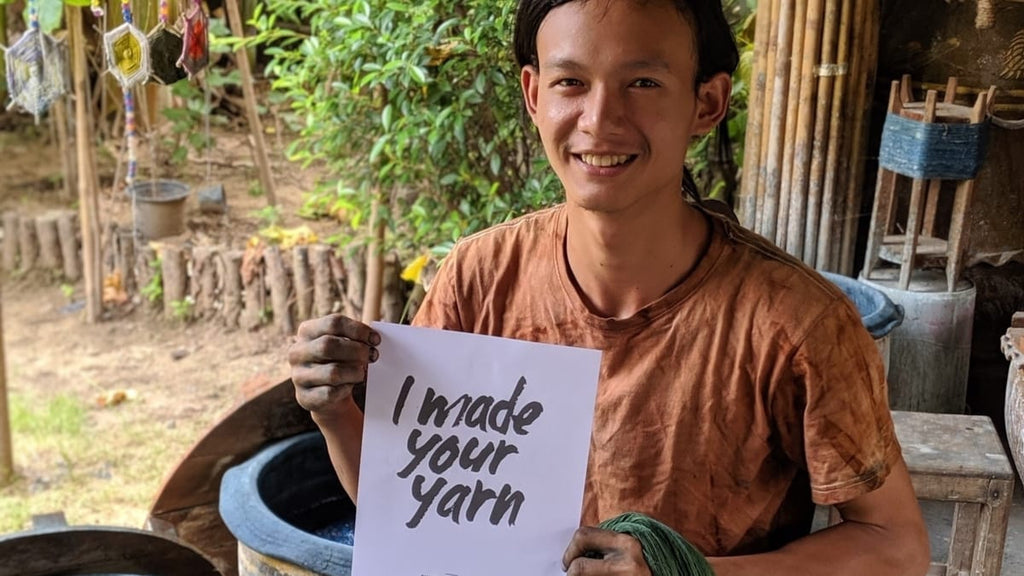 """A male artisan from Tohsang Cotton Village sits in front of his dye bath holding a """"I made your yarn"""" sign. He is holding recently dyed sustainable cotton in olive green used in the Cherrada dress by Rare & Fair."""