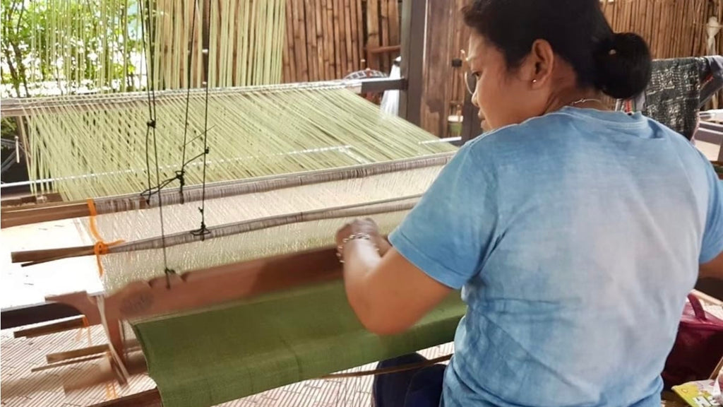 An artisan from Tohsang Cotton Village sitting at her loom weaving sustainable cotton fabric in olive green for the Cherrada dress by Rare & Fair.