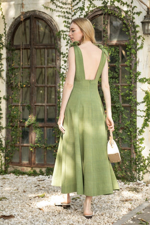 Model walking outside wearing the handmade cherrada midi dress by Rare & Fair,  made from sustainable cotton and naturally dyed in olive green.