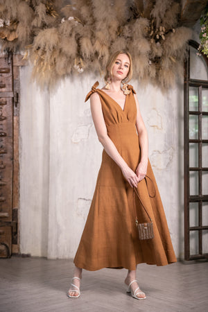 Model walking inside wearing the handmade cherrada midi dress by Rare & Fair,  made from sustainable cotton and naturally dyed in burnt sienna..