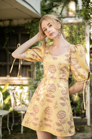 The model is wearing the handmade pure silk Ikat dress in mellow yellow with floral design by Rare & Fair.