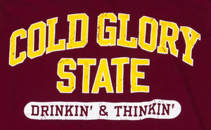 Close-up of Maroon or Burgundy and Gold Collegiate Varsity T-shirt. Distressed printing of college or university  name and Drinking and Thinking sport.