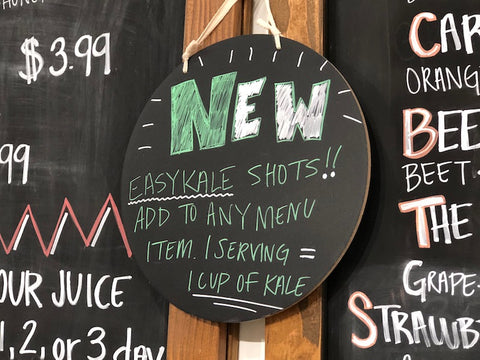 A chalkboard that says New! EasyKale Shots. Add to any menu item. 1 serving equals 1 cup of kale.