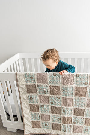 baby-boy-playing-in-crib-with-brown-blue-neutral-tone-minimalist-baby-blanket