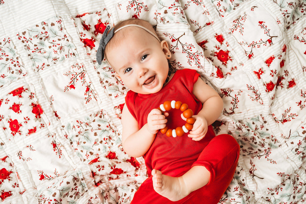 new-baby-girl-in-red-jumper-playing-with-wood-toy-on-christmas-blanket-by-sugar-owl-design