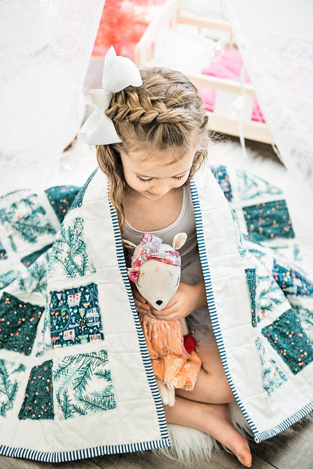 little-girl-with-braided-bow-hair-holding-doll-under-christmas-quilt