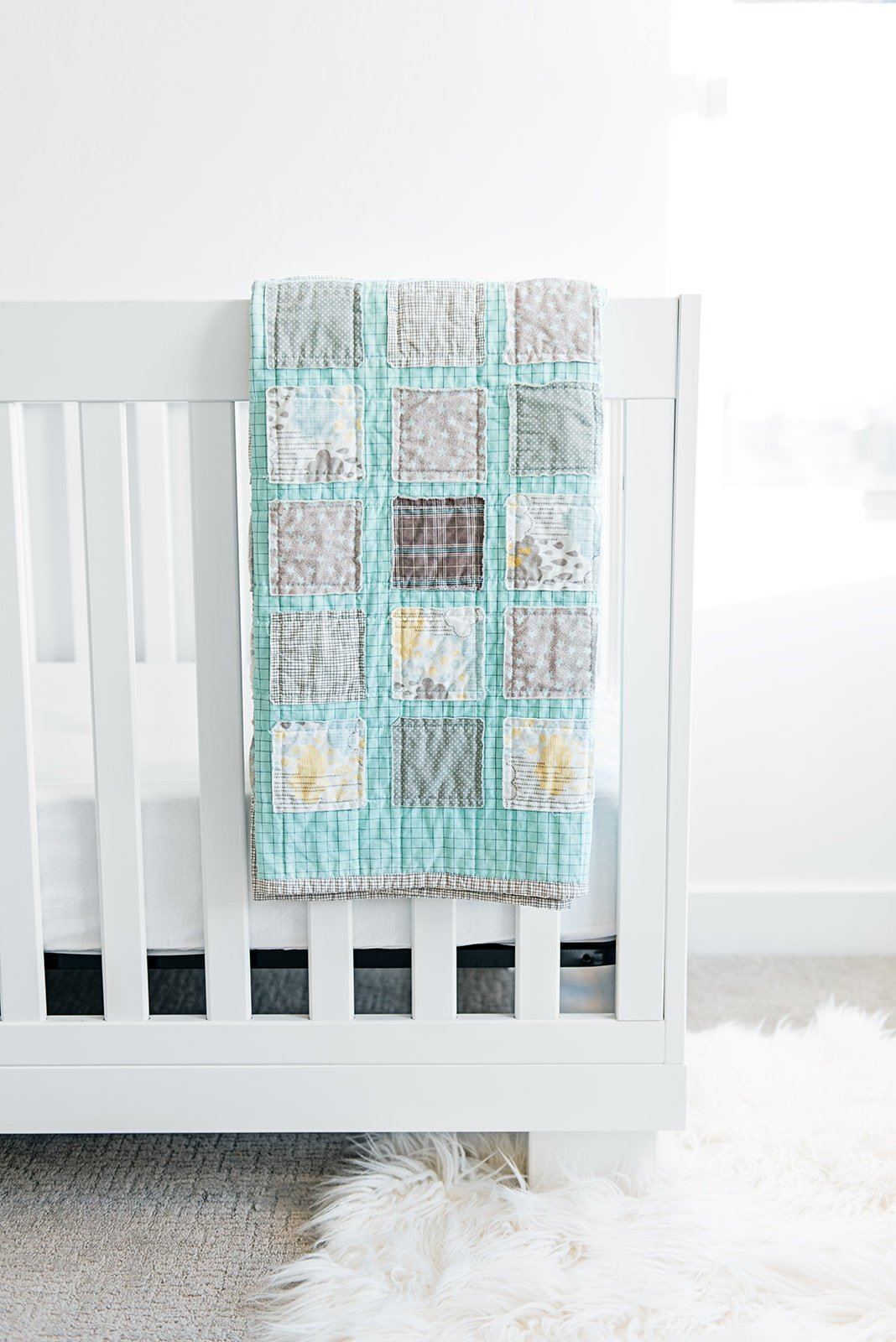 gender-neutral-baby-room-with-handmade-quilt-hanging-over-white-crib