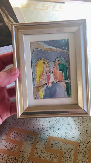 Video of small approximately 4 inch tall framed watercolor painting of two adult birds and one baby bird sitting on a limb. The birds are each a different color, yellow, green, and light red.