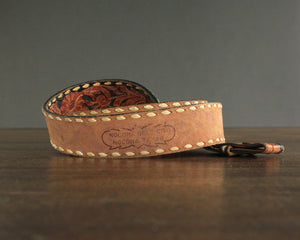 Vintage tooled leather belt with white lacing and floral pattern