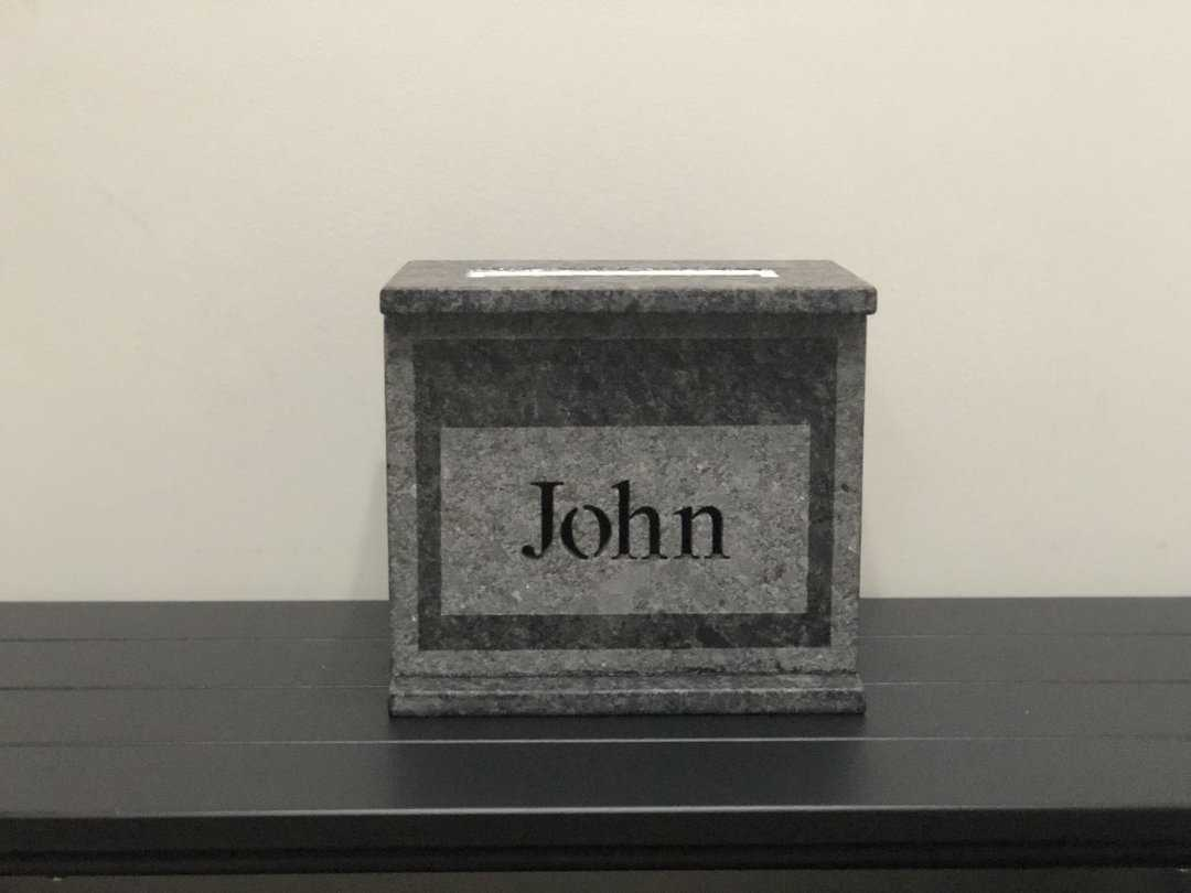 "Grey cremation urn with the name ""John"" engraved."