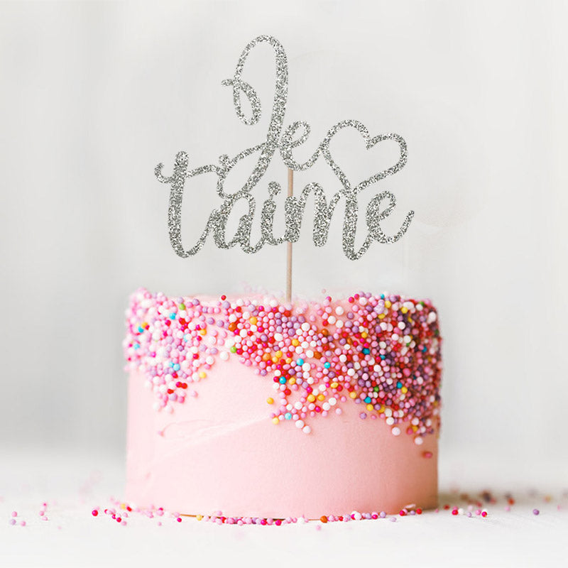 Je t'aime I love you wedding engagement silver cake topper on top of pink cake