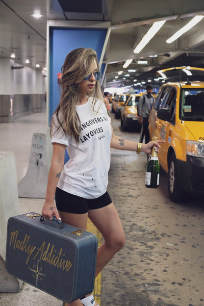 Female Traveller wearing Hangovers and Layover tee as she leaves the airport on a taxi.