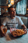 Male Traveller wearing Hangovers and Layover tee as he eats and drinks beer in a diner.