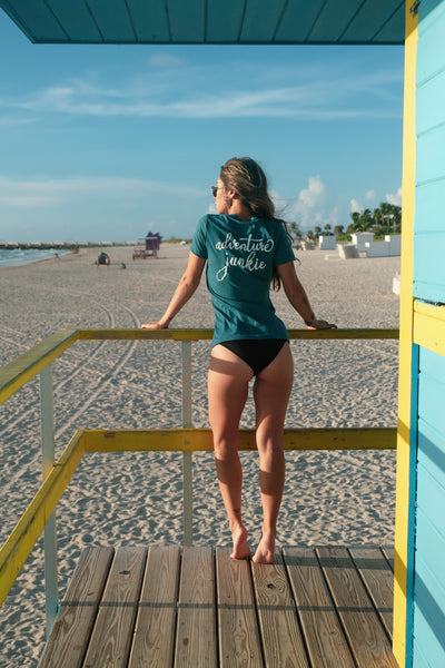 Female wearing Madly Addictive Adventure Junkie Tee on a lifeguard stand on the beach.