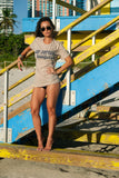 Female Traveller wearing Jet Setting Bombshell Tee on the beach