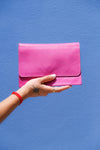 Female traveller holding the pink Madly Addictive adjustable purse which can be worn as a cross body, belt bag and used as a clutch or a wallet.