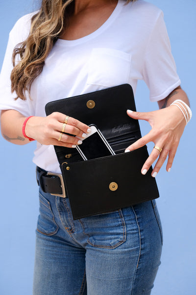 Female traveller wearing the Madly Addictive adjustable purse which can be worn as a cross body, belt bag and used as a clutch or a wallet.