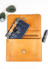 Travel accessories in a Cognac leather cross body, belt bag, clutch and wallet.