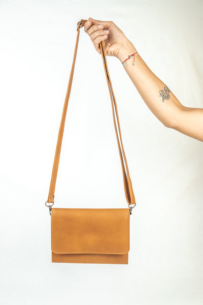 Female holding a Cognac leather cross body, belt bag, clutch and wallet.