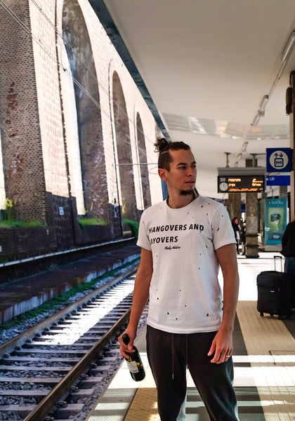 Male Traveller wearing Hangovers and Layover tee as he waits in the train station airport with a wine bottle in his hand.