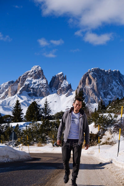 Male Traveller wearing Hangovers and Layover tee as he walks down the road with the Dolomites mountain view background.
