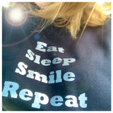 Black sweat shirt with silver writing. Eat, sleep, smile, repeat.