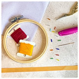 Picture of all the materials. Hoops, pink and yellow thread, pen, hoop, glass beads, ribbon for hanging, and 14 count aida material
