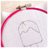 Picture of aida fabric in a hoop, with the needle coming through the fabric from the back