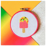Picture of a finished pink and yellow cross stitch lollipop, with glass bead sprinkles