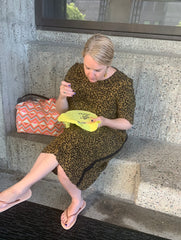 Girl sitting sewing on a bench