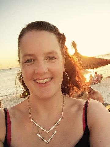 Girl with brown hair, smiling and looking into the camera, with the sunset behind her.