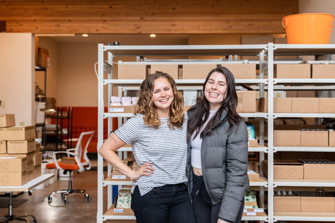Photo of Genevieve and Marimar, co-owners of Eco Collective, standing and smiling the warehouse