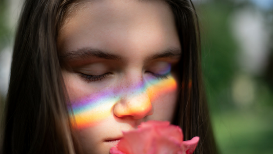 Woman smelling a rose with rainbow reflecting on her face