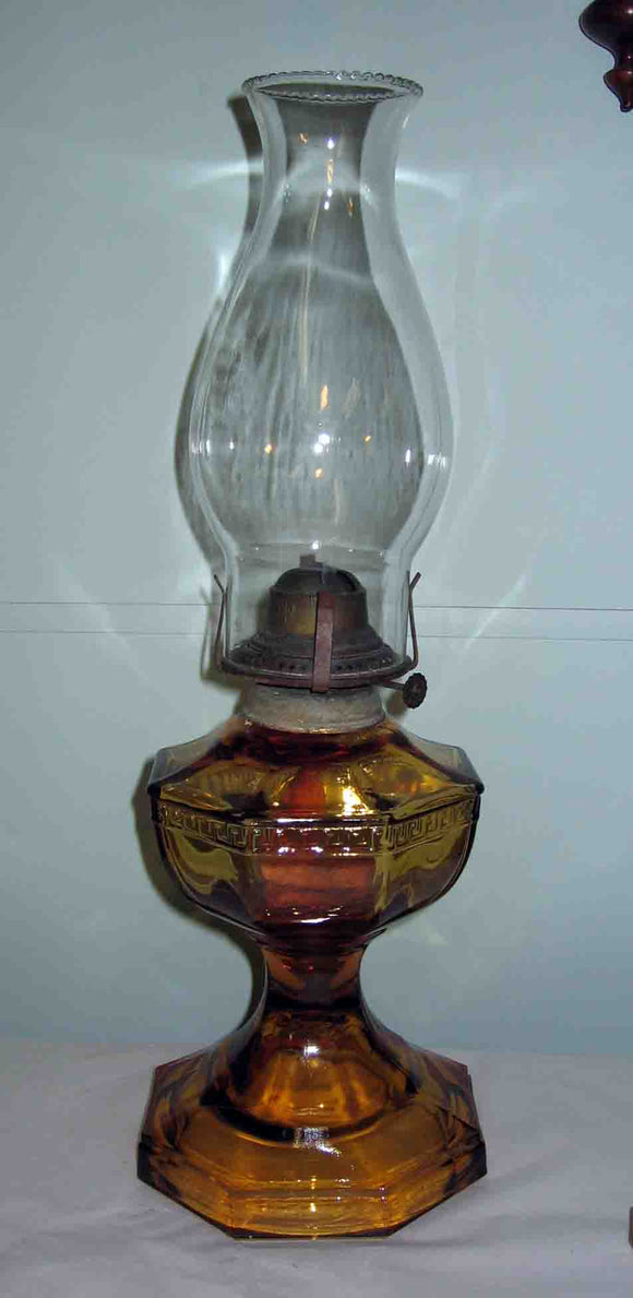 Greek Key pattern single burner oil lamp with amber glass font.
