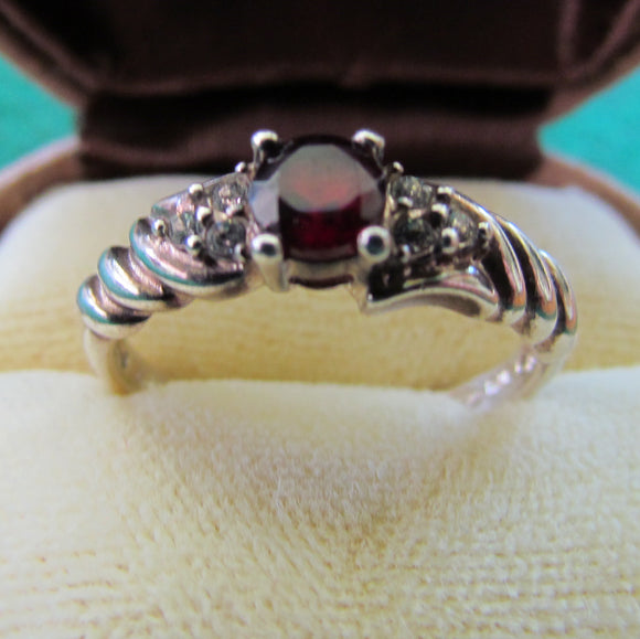 925 Sterling Silver Dress Ring Set With A Garnet Having Clear Shoulder Stones