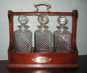 Oak cased 3 bottle Tantalus with plated mounts and original key