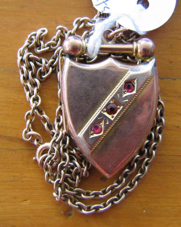 Victorian 9ct yellow & rose gold shield shaped photo locket /  pendant with chain set with 3 red stone assumed as garnets.