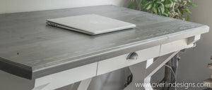HANDCRAFTED CARBON GRAY AND ALABASTER FARMHOUSE TRESTLE DESK WITH LAPTOP ON TOP