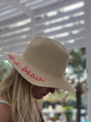 ladies panama hat with bright pink writing on the side 'lifes a beach'