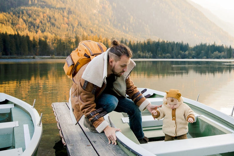 A Baby with Dad standing in a boat near lakes in the mountain