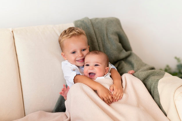 Happy toddler with his sibling