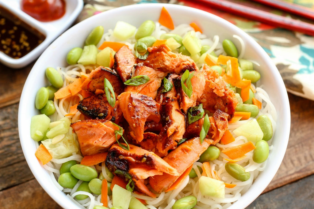Asian Style Salmon Noodle Bowl is a quick and easy dinner idea with sockeye salmon marinated and pan seared over rice noodles with edamame, carrots, and cucumbers.