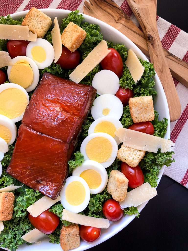 Side view with whole portion of smoked salmon with all the salad ingredients.
